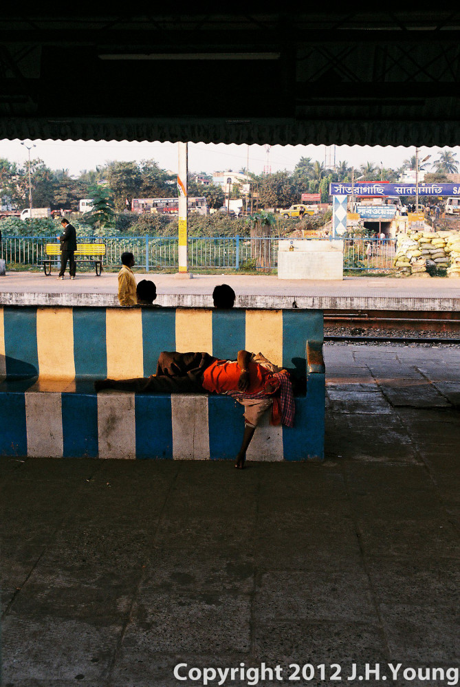 man waiting for a train in india