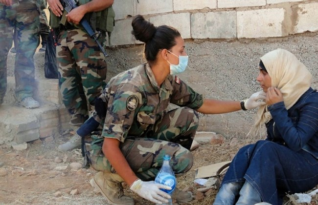 A female member of the Lebanese Army helps a Syrian refugee entering the town of Arsal after spending around two days on the outskirts with no food. (The Daily Star/Lebanese Army HO)