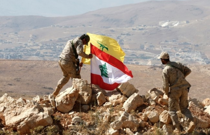 Hezbollah fighters set a Lebanese and the party s flags during a guided tour in a mountainous area around the Lebanese town of Arsal along the border with Syria, Tuesday, July 25, 2017. (The Daily Star/Mohammad Azakir)